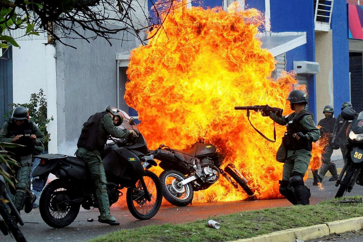 Riot security forces clash with demonstrators as a motorcycle is set on fire during a protest against Venezuelan President Nicolas Maduro's government in San Cristobal, Venezuela May 29, 2017. PHOTO: REUTERS