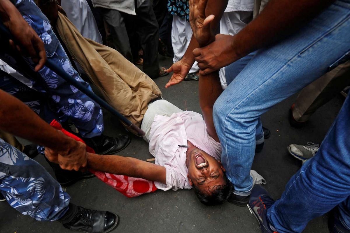 Police detain an activist from the All India Democratic Students Organisation (AIDSO) during a demonstration against what the protestors say is to abolish no-detention policy and reintroduce the pass-fail system in the schools of West Bengal state, i