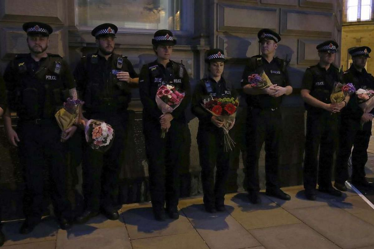 Police officers paying their respects for the victims of the Manchester bombing during a vigil at St Ann's Square in Manchester, Britain, on May 29, 2017.