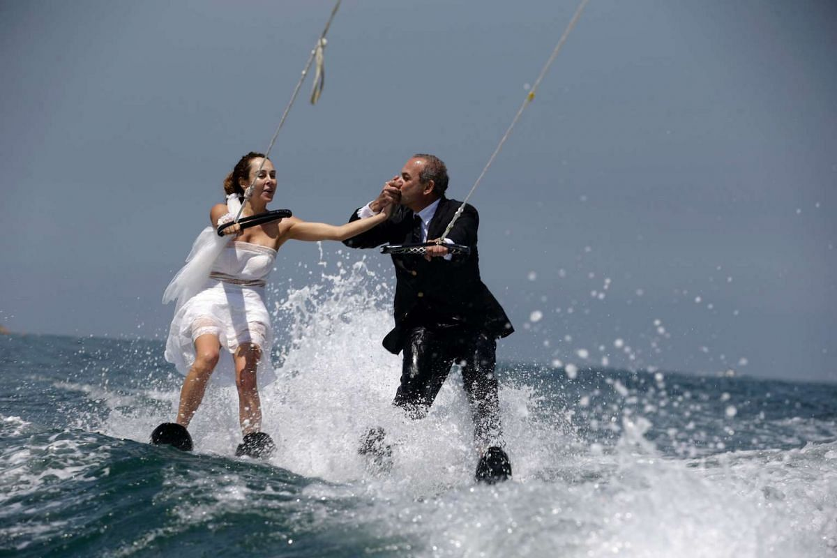 Lebanese groom Tommy kisses the hand of his bride Nadine's while water skiing dressed in their wedding clothes in the waters off the bay of Jounieh, north of Beirut, on May 29, 2017. PHOTO: AFP