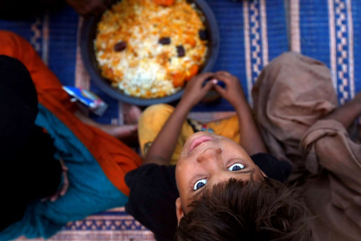 A boy sits with others as they wait to break their fast at a charity food distribution point along a road during a Muslim holy month of Ramadan in Karachi, Pakistan May 29, 2017. PHOTO: REUTERS