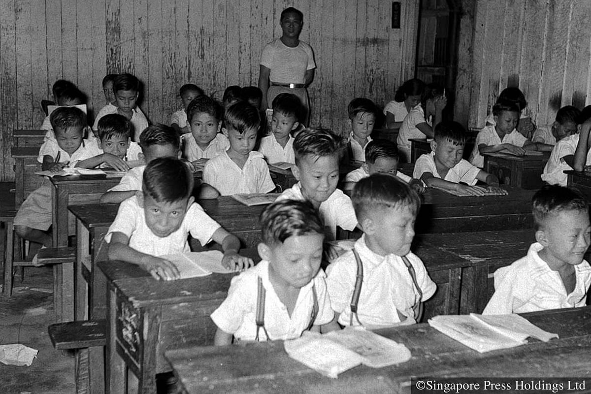 1956: Three students shared a table and a long wooden bench in class.