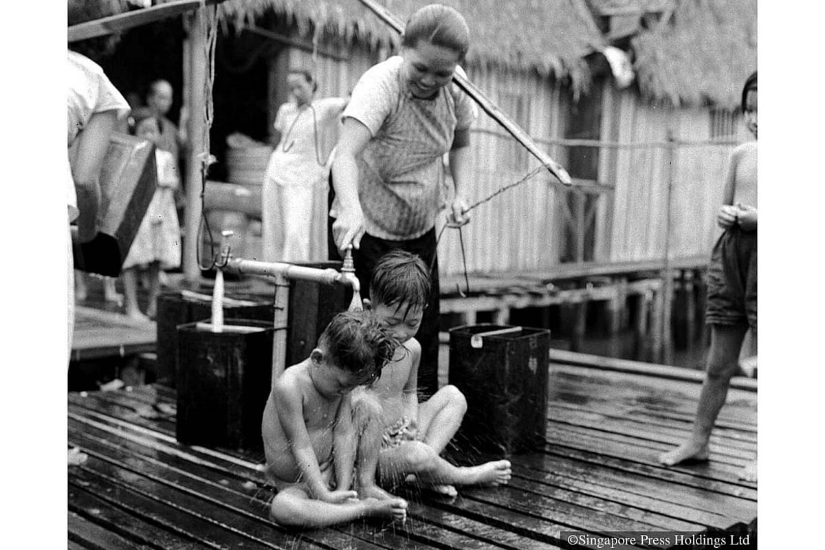 1956: With no direct water supply to their huts, children had to bathe at the village water pump.