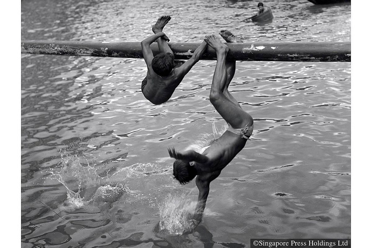 """1954: Boys taking part in the Sea Sports Carnival where they had to """"fight"""" while sitting on a long beam covered with grease."""