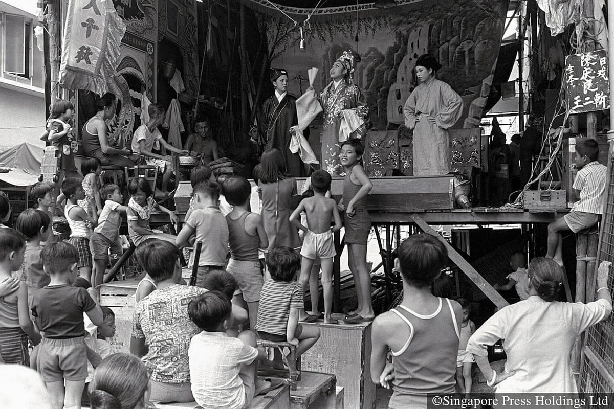 """1952: Children enjoy the wayang (Chinese opera) performance by taking up """"first class"""" position in front of the stage."""