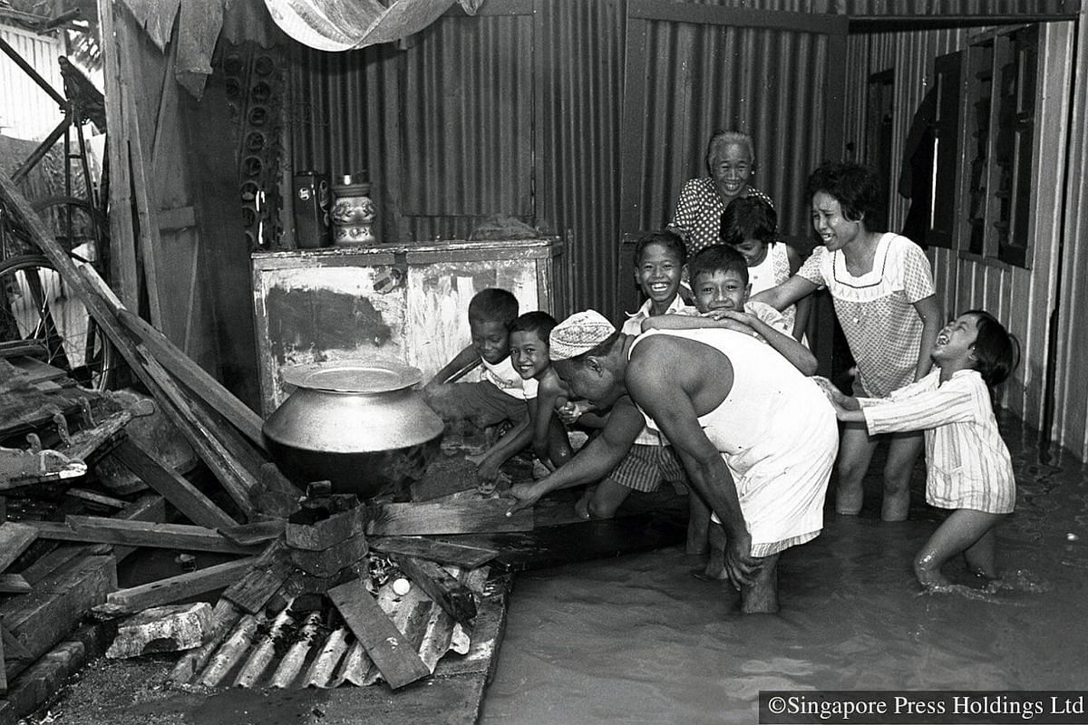 1973: The knee-high flood water did not dampen the spirits of these children who cheerfully helped to prepare food for Hari Raya Puasa.