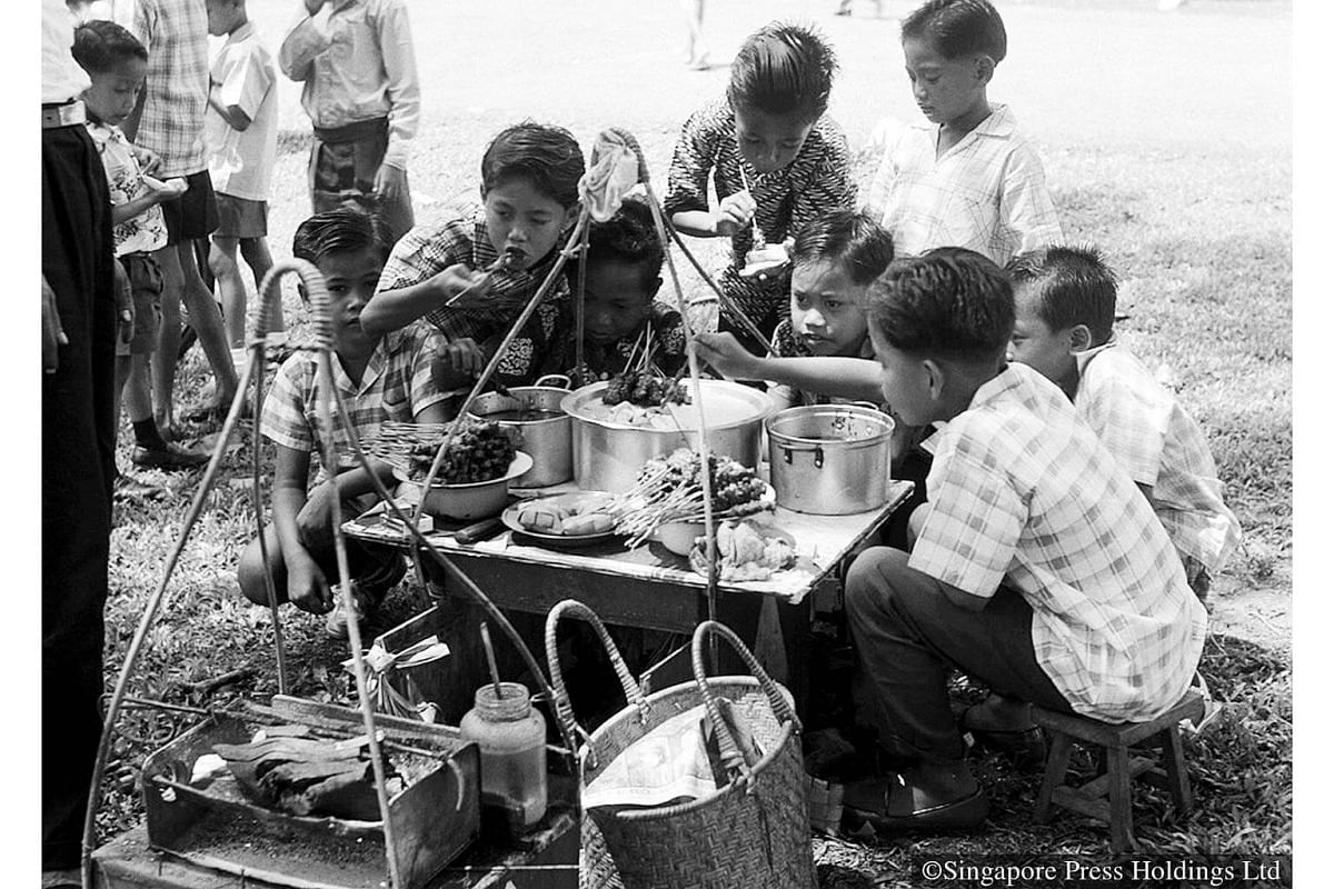 1961: Boys eating satay from a makeshift roadside stall during their Hari Raya Puasa outing to the National Museum.