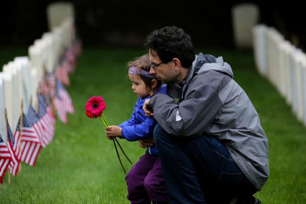 US Marine and Iraqi war veteran Croft Young and his daughter Evelyn, three, at the gravesites of US Military veterans on Memorial Day at the Cypress Hills National Cemetery in Brooklyn. PHOTO: EPA