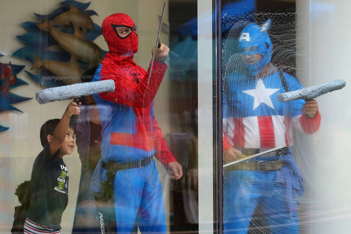 Four-year old Dominic helps window-washers dressed as superheroes as they work at Rady Children's Hospital in San Diego, California, U.S., May 30, 2017. PHOTO: REUTERS