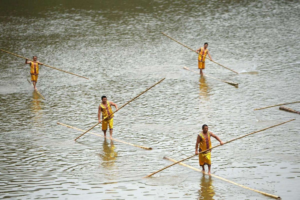 A photo released on May 30, 2017 shows participants paddling on bamboo poles as they take part in a performance ahead of the Dragon Boat festival at Tanghe Town in Chongqing, China, May 27, 2017. PHOTO: REUTERS/HANDOUT