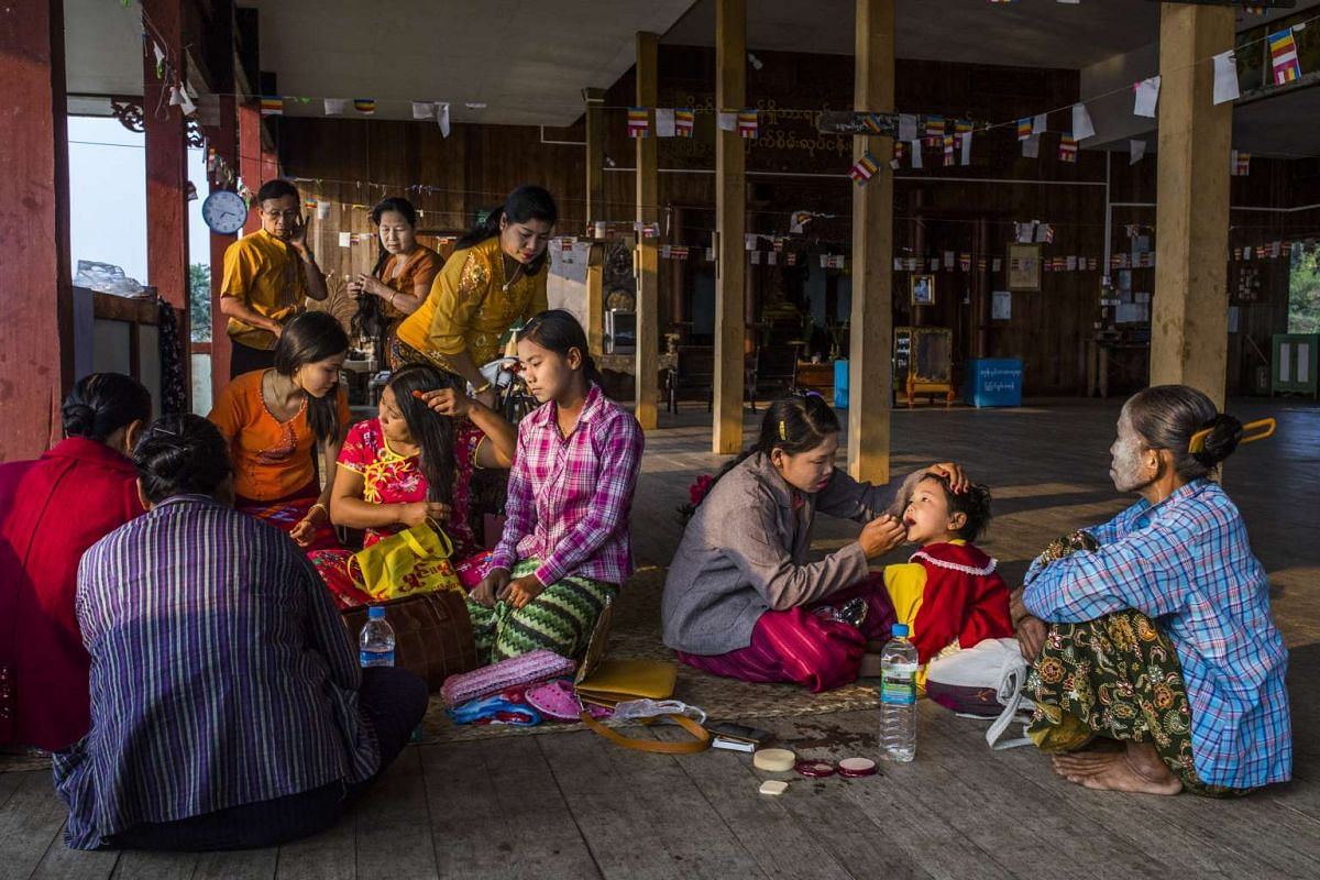 Women and children put on Thanaka paste and dress up at a Buddhist temple hall before going to Shwemyitzu Pagoda on the Indawgyi Lake in Myanmar.