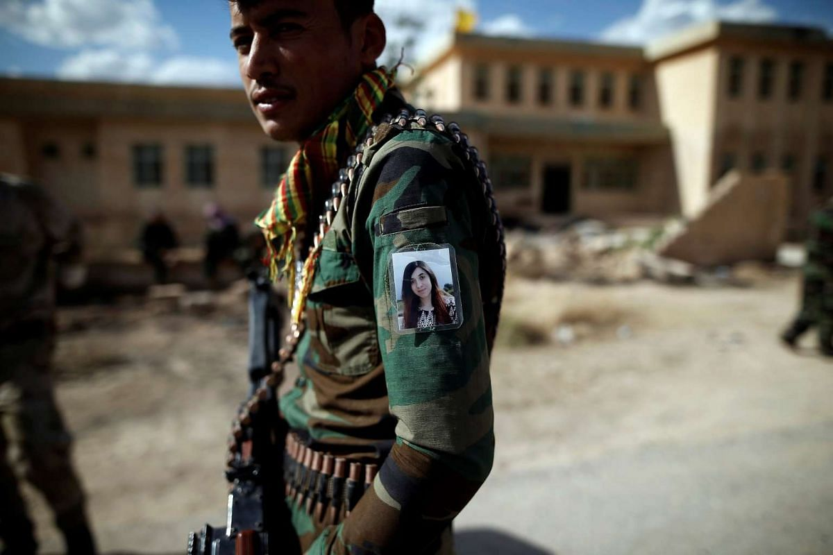 Yazidi Popular Mobilisation Forces (PMF) fighter Hussein Eisso, 21, hangs a photo of Yazidi survivor and United Nations Goodwill Ambassador for the Dignity of Survivors of Human trafficking Nadia Murad on his arm in Kojo, Iraq June 1, 2017. PHOTO: RE