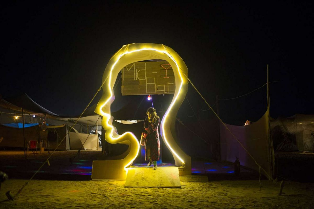 A festivalgoer stands next to an art installation at night during the Israel Midburn Festival in the Negev desert southern Israel on May 31, 2017.