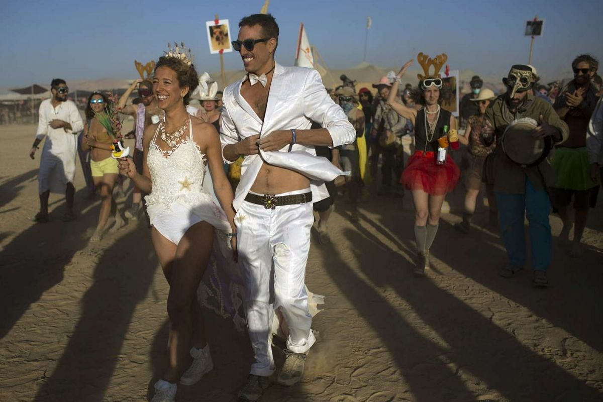 Festivalgoers during a wedding ceremony at the Israel Midburn Festival in the Negev desert southern Israel on May 31, 2017.