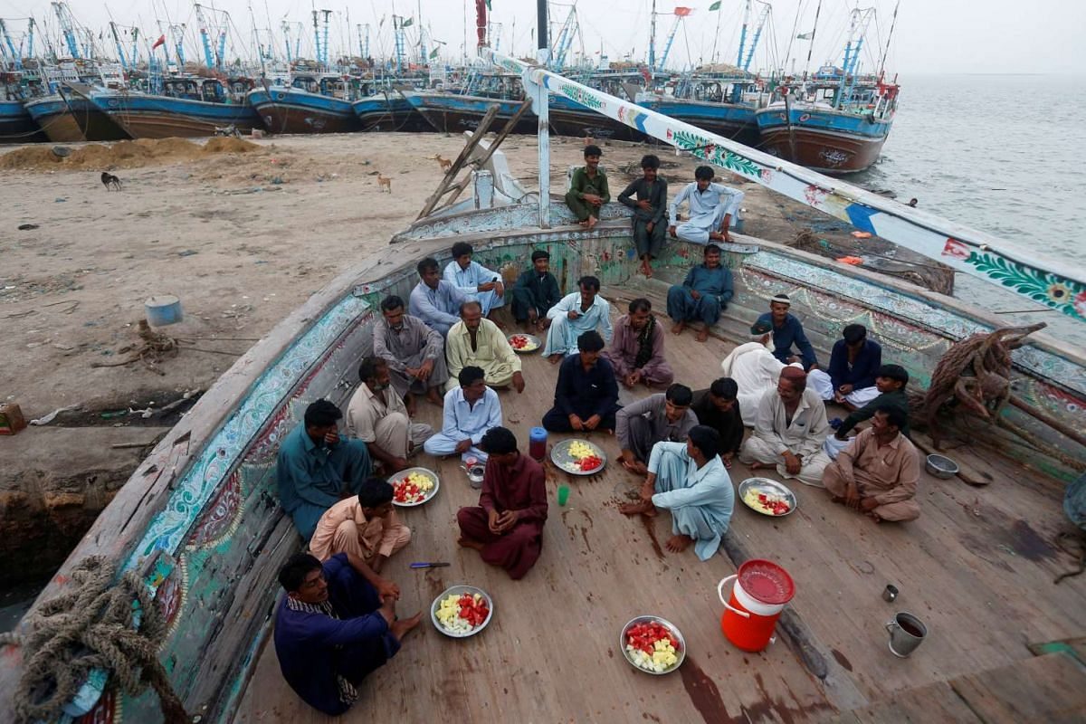Fishermen sit on a fishing boat as they prepare to break their fast during a Muslim holy month of Ramadan in Ibrahim Hyderi, on the outskirts of Karachi, Pakistan June 1, 2017. PHOTO: REUTERS