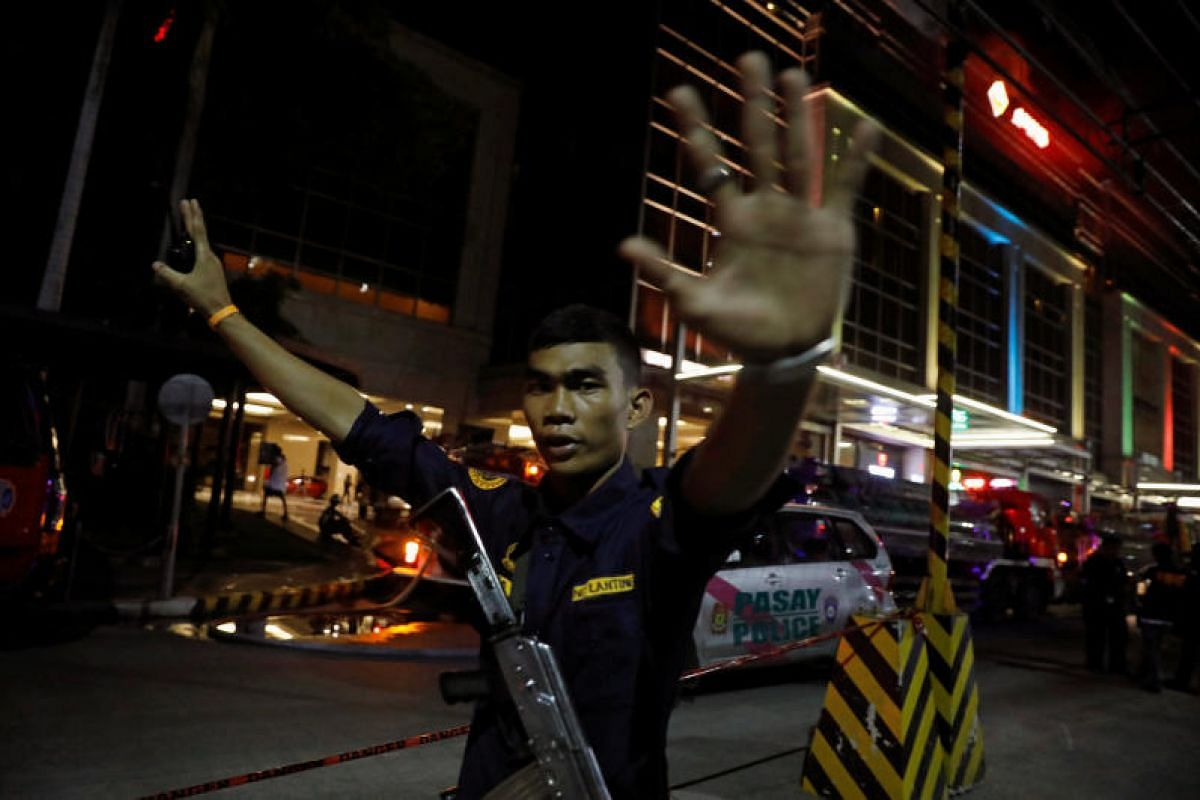 A security guard stops photographers from entering the vicinity of Resorts World Manila after gunshots and explosions were heard.