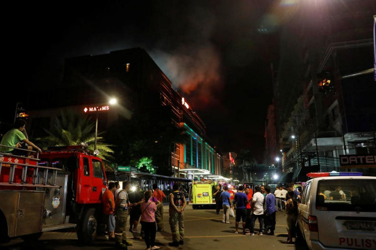 Evacuated employees and guests of hotels stand along a road and watch as smoke billows from the hotel.