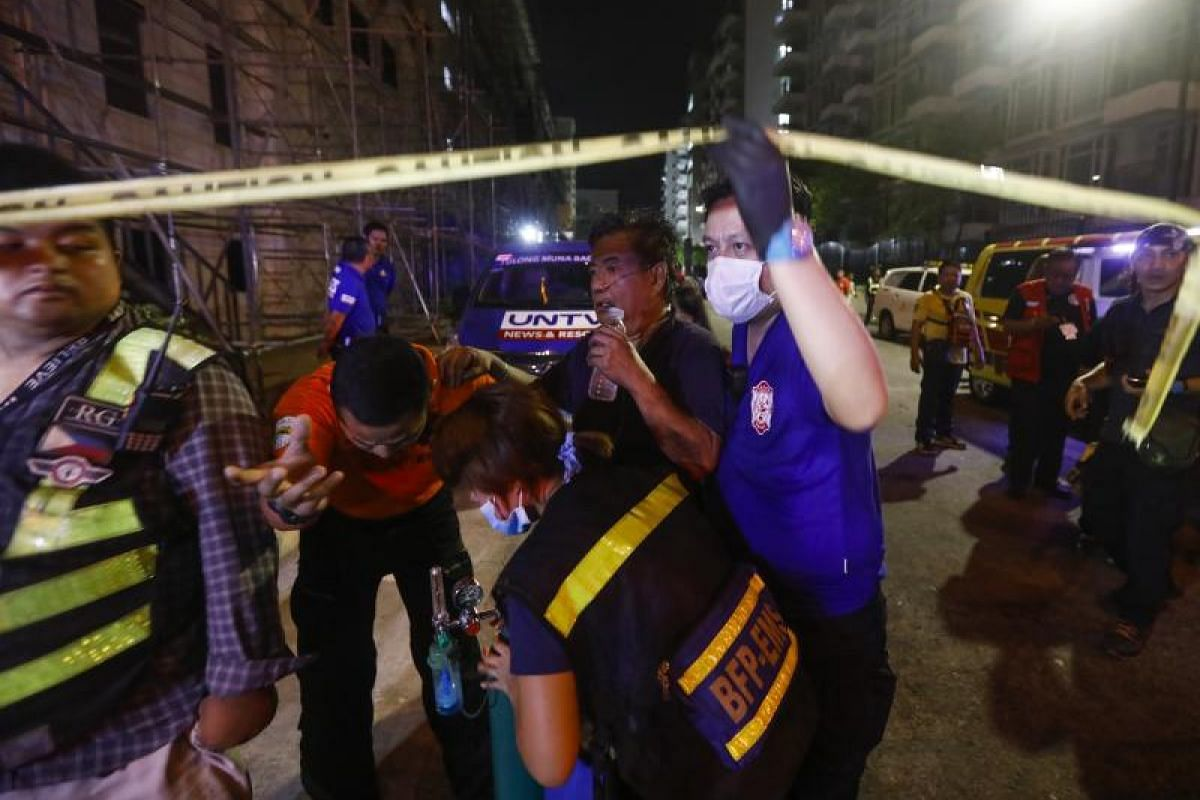 A civilian (second from right) receiving treatment from medical responders is evacuated from behind the hotel.