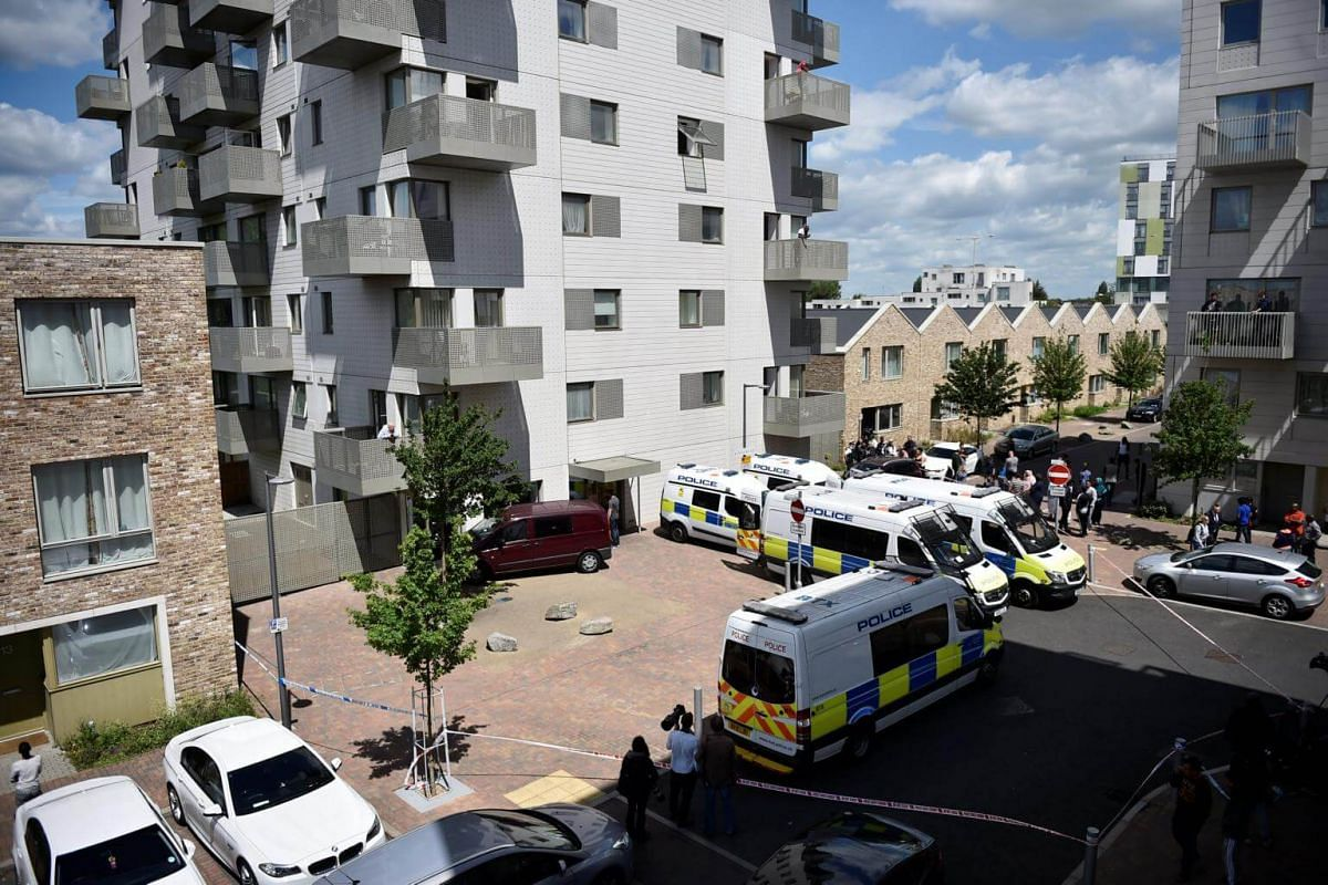 Police vehicles seen outside a block of flats after police launched an operation to raid the building, in Barking, London, on June 4, 2017.