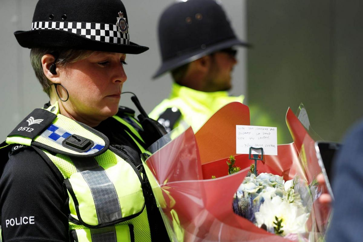 A police officer carrying a bouquet of flowers with a message of sympathy, near Borough Market, on June 4, 2017.