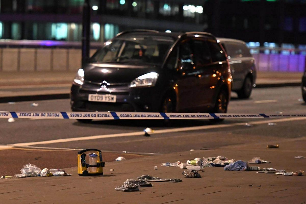 Debris is seen strewn across the road in front of abandoned vehicles, following an apparent terror attack on London Bridge, on June 3, 2017.