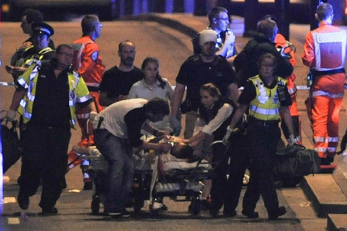 Police and members of the emergency services attend to victims of a terror attack on London Bridge in central London on June 3, 2017.