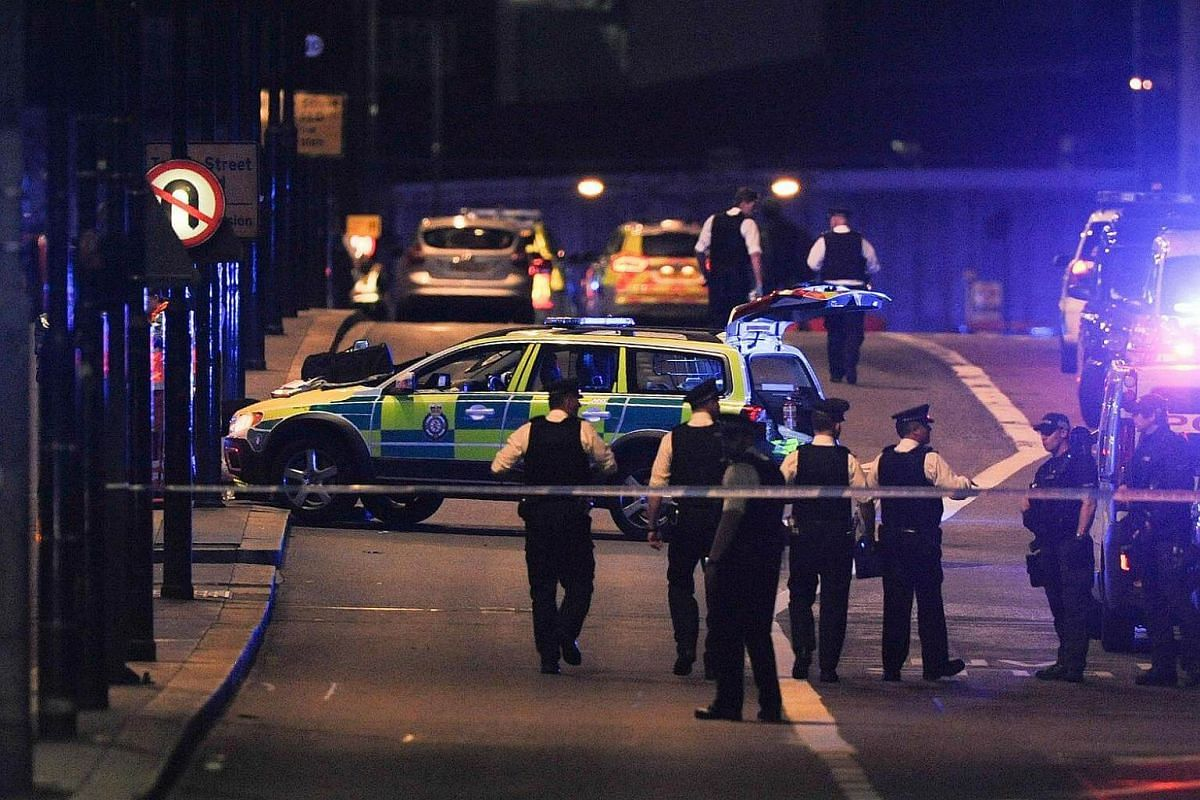 Police officers walk at the scene of an apparent terror attack on London Bridge in central London on June 3, 2017.