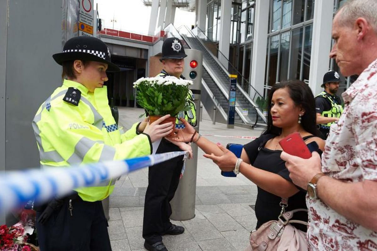 A woman asking a police officer to lay flowers outside The Shard in the London Bridge quarter in London on Sunday (June 4), as a tribute to the victims of the June 3 terror attack.