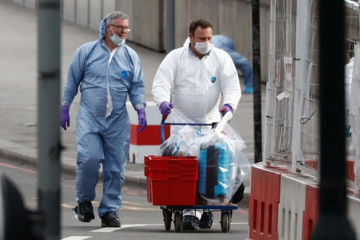 Police forensics officers with containers of evidence as investigations into the attack continue.
