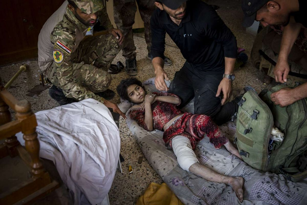 Iraqi special forces soldiers treat a girl who was injured when her house was hit by an airstrike in the Saha neighborhood of Mosul, Iraq on May 29, 2017.