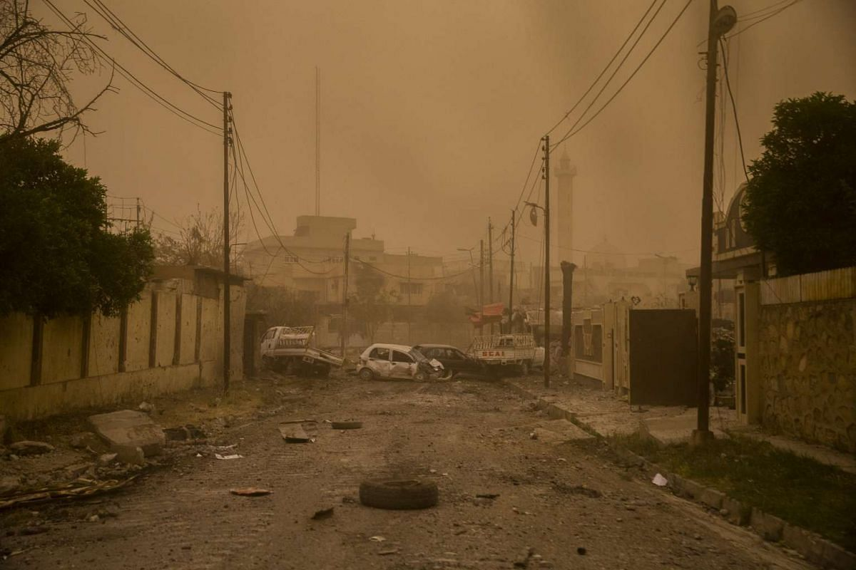 Vehicles block the edge of the frontline in the Rifai neighborhood of Mosul, Iraq, seen through the window of a military vehicle as a sandstorm moves in, May 19, 2017.