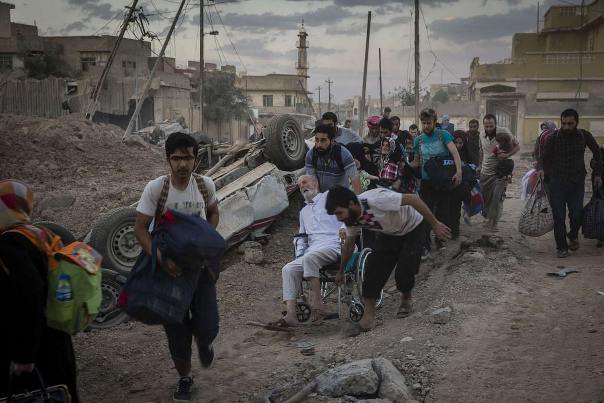 Civilians flee across a junction that a sniper was targeting in the Rifai neighborhood of Mosul, Iraq, May 20, 2017.
