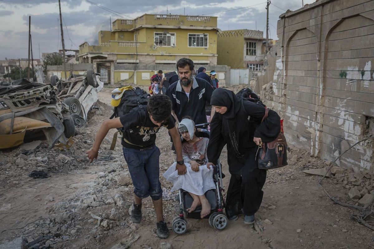Civilians run across a junction that a sniper is targeting, in the Rifai neighborhood of Mosul, Iraq on May 20, 2017.