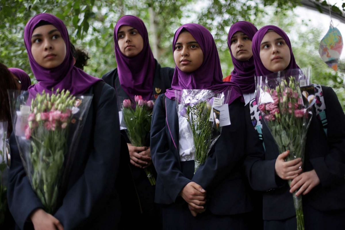 Pupils from Eden Girls' School in Walthamstow hold flowers at Potters Fields Park in London on June 5, 2017, during a vigil to commemorate the victims of the terror attack on London Bridge and at Borough Market that killed seven people on June 3. PHO