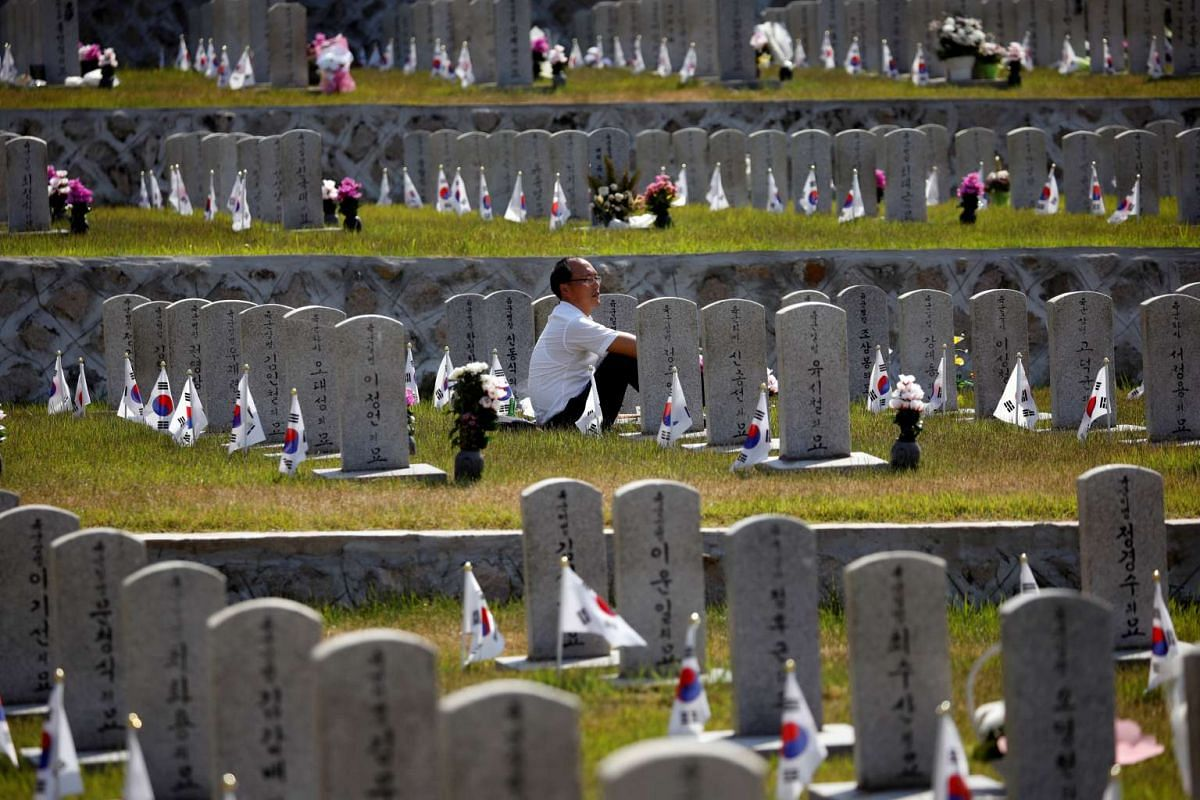 A man sits in front of the gravestone of a family member who died for the country, on the eve of South Korea's Memorial Day, at the national cemetery in Seoul, South Korea, June 5, 2017. PHOTO: REUTERS