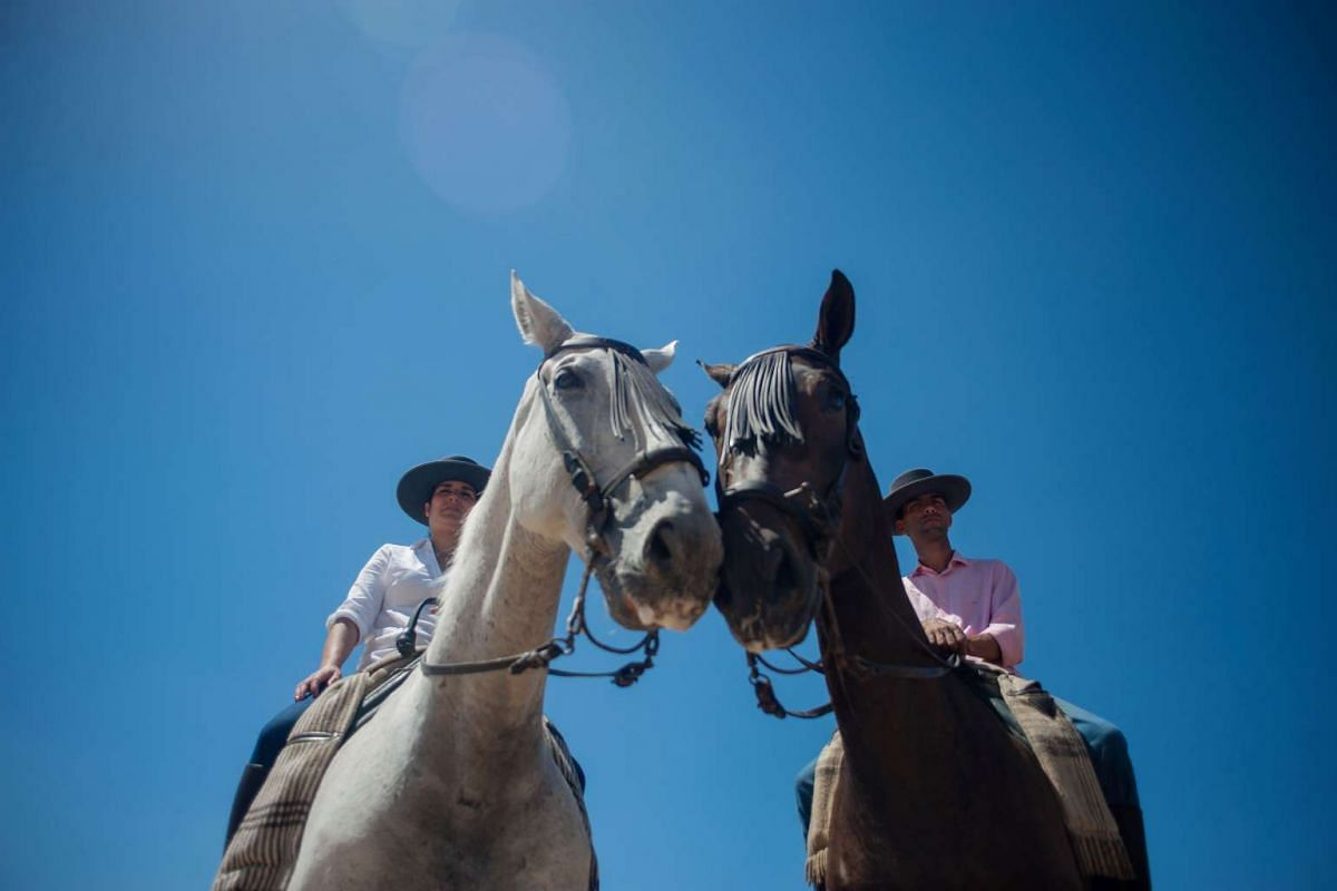 Pilgrims sit on horses during a pilgrimage in the village of El Rocio, southern Spain on June 5, 2017. PHOTO: AFP