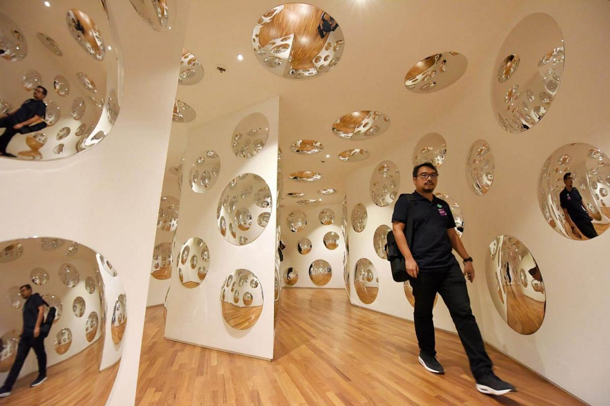 A member of the media walks through the installation entitled Invisible Life (2017), made up of reflective acrylic convex discs.