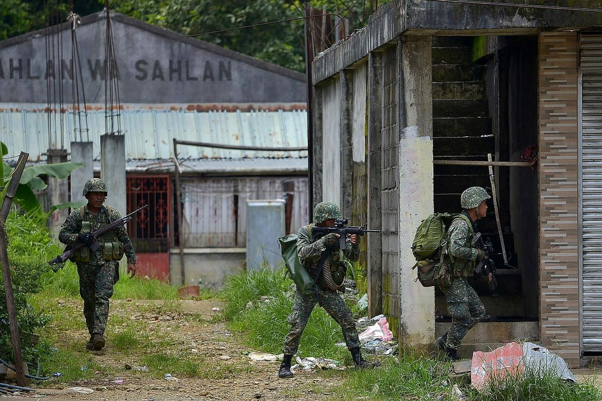 Philippine marines about to launch an assault on an Islamist militants' hideout in Marawi on the southern island of Mindanao last Saturday. Almost 180 people have died since the siege began. Displaced villagers taking shelter at a gymnasium turned in