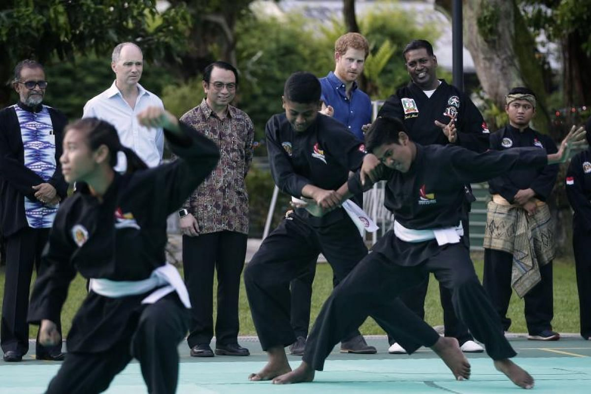 Prince Harry watching with Jamiyah's silat coach Sheikh Alauddin Yacoob Marican (second from right) a silat demonstration, performed by residents of Jamiyah Singapore and representatives from the Silat Federation, at Jamiyah Singapore on Sunday (June