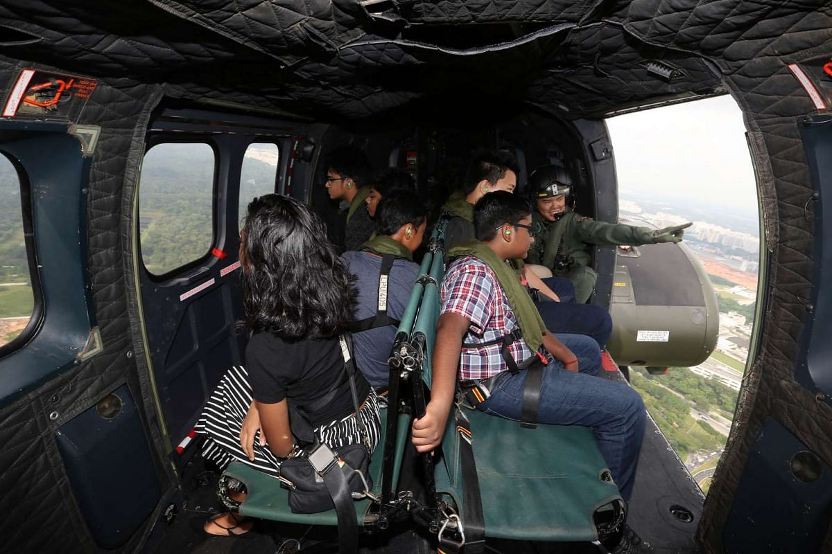 Seven beneficiaries of The Straits Times School Pocket Money Fund were given a treat on board a Super Puma helicopter on June 6, 2017. They were on board to watch the flypast of the state flag that was being flown by a Chinook helicopter for National