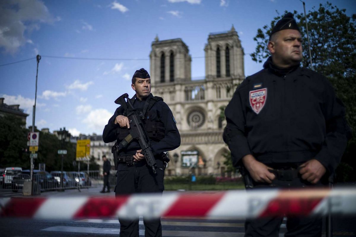 French police officers stand guard outside of the Notre Dame cathedral after a man attacked a police officer with a hammer, in Paris, France, June 6, 2017. The assaillant has been shot and injured by police. PHOTO: EPA