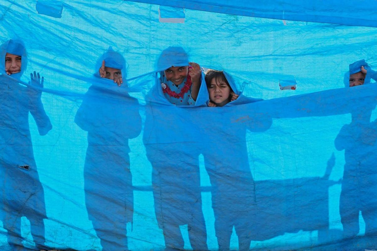 Iraqi children peer through a tarpaulin as they collect water from a tank at the Al-Khazir camp for internally displaced people, located between Arbil and Mosul, on June 6, 2017. PHOTO: AFP