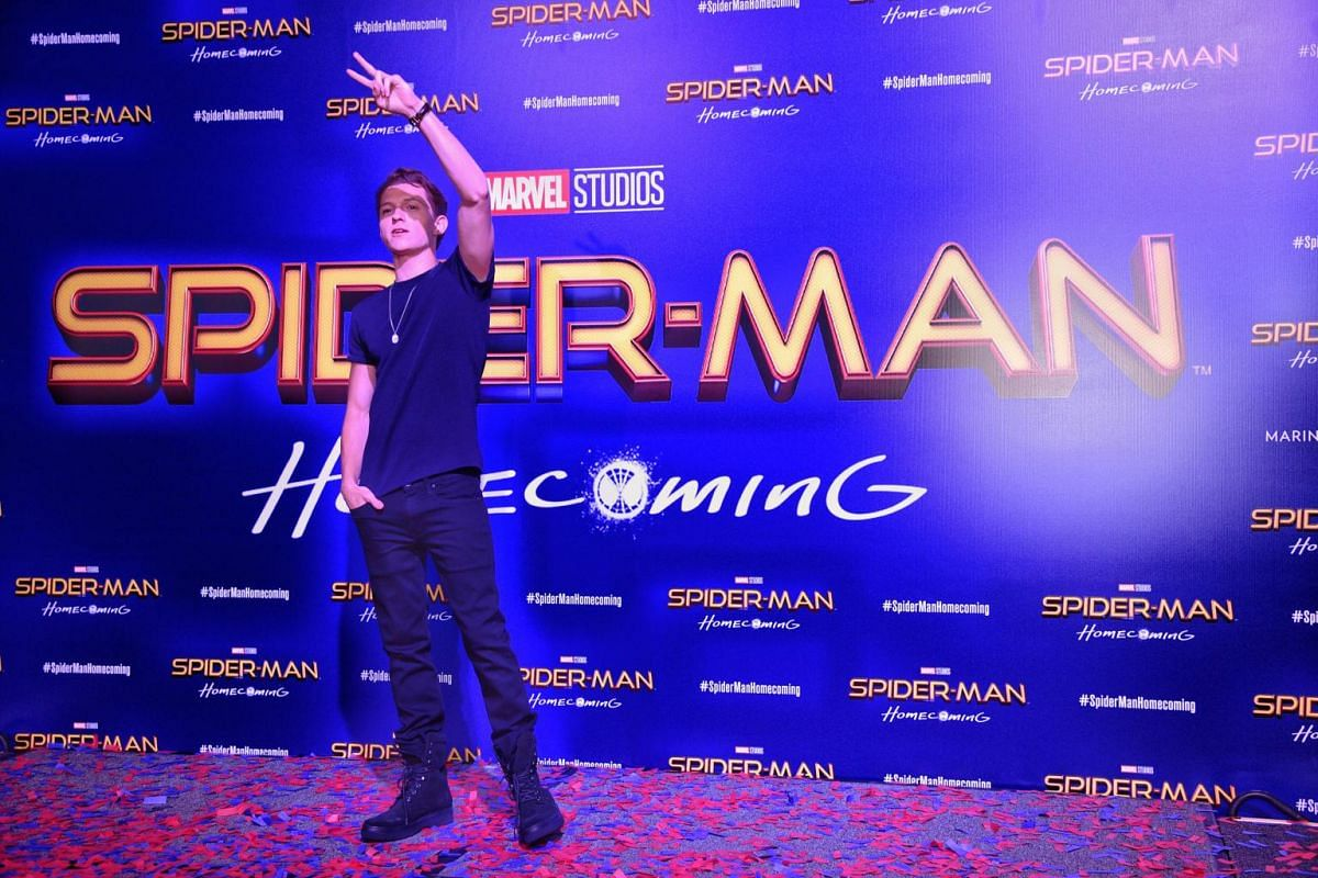 Tom Holland on stage greeting the fans at the Spider-Man movie red carpet.
