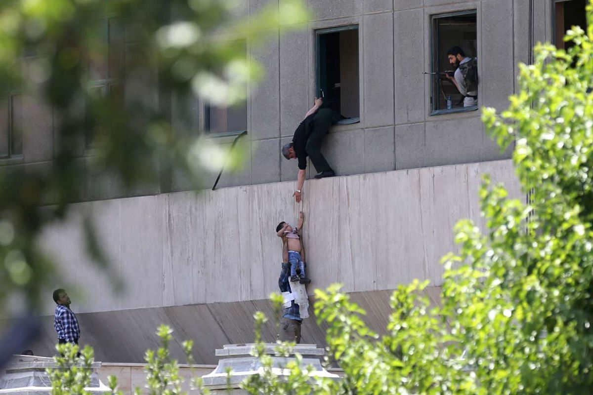 Iranian policemen evacuate a child from the parliament building in Tehran, Iran, on June 7, 2017 during an attack on the complex. PHOTO: AFP/FARS NEWS