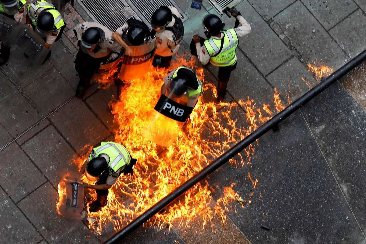 Riot security forces members catch fire during riots at a rally against Venezuelan President Nicolas Maduro's government in Caracas, Venezuela, June 7, 2017. PHOTO: REUTERS
