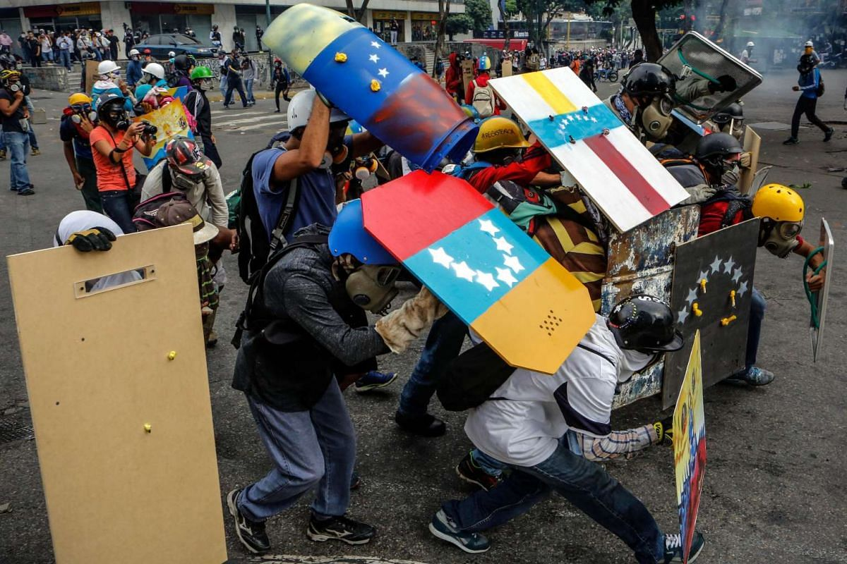 Opposition sympathizers hide behind homemade shields during a protest in Caracas, Venezuela, June 7, 2017. PHOTO: EPA