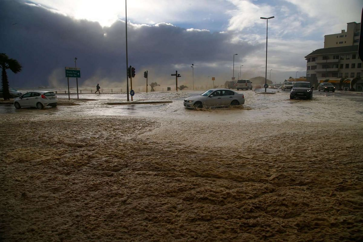 Cars move along a flooded road on Seapoint promenade during a storm in Cape Town, South Africa on June 7, 2017.