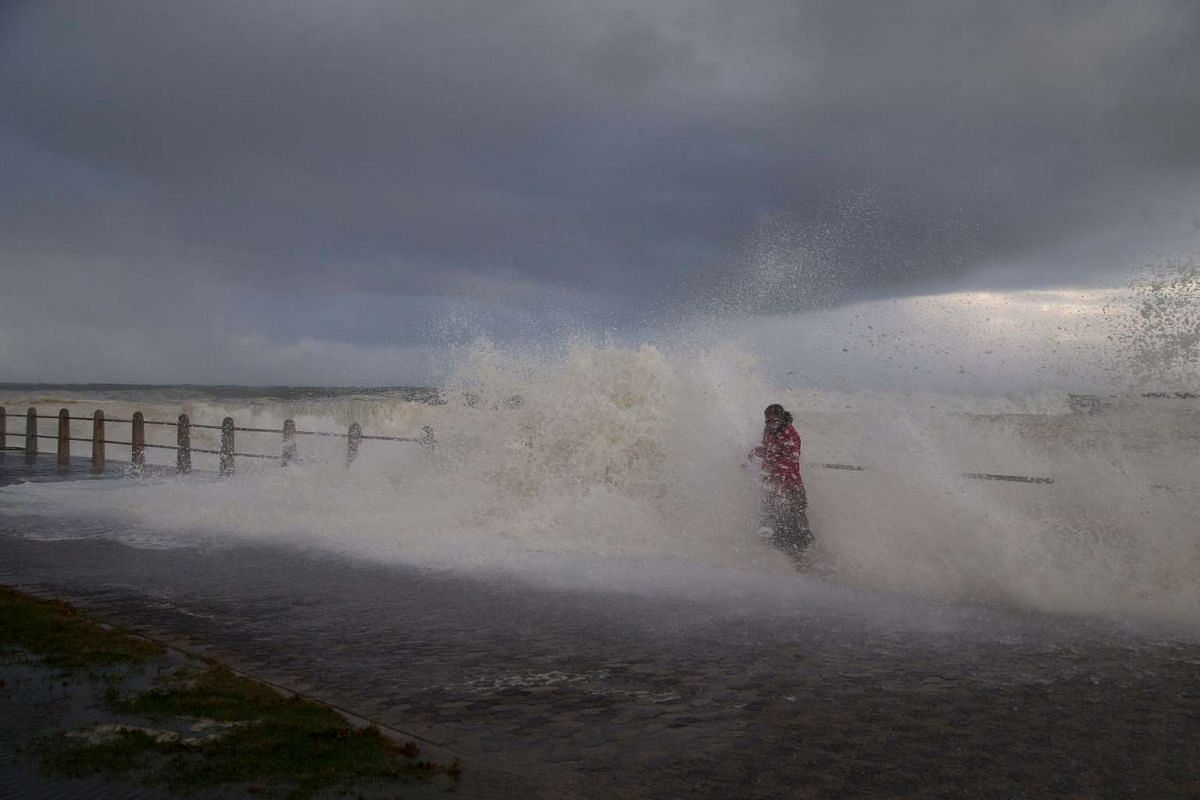 A woman is engulfed by a wave as she walks along Seapoint promenade during a storm in Cape Town, South Africa on June 7, 2017.