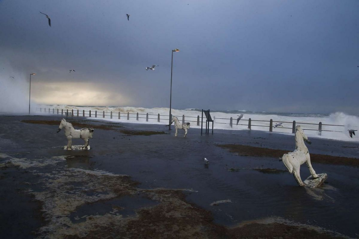 Gulls fly over sculptures along the flooded Seapoint promenade during a storm in Cape Town, South Africa on June 7, 2017.