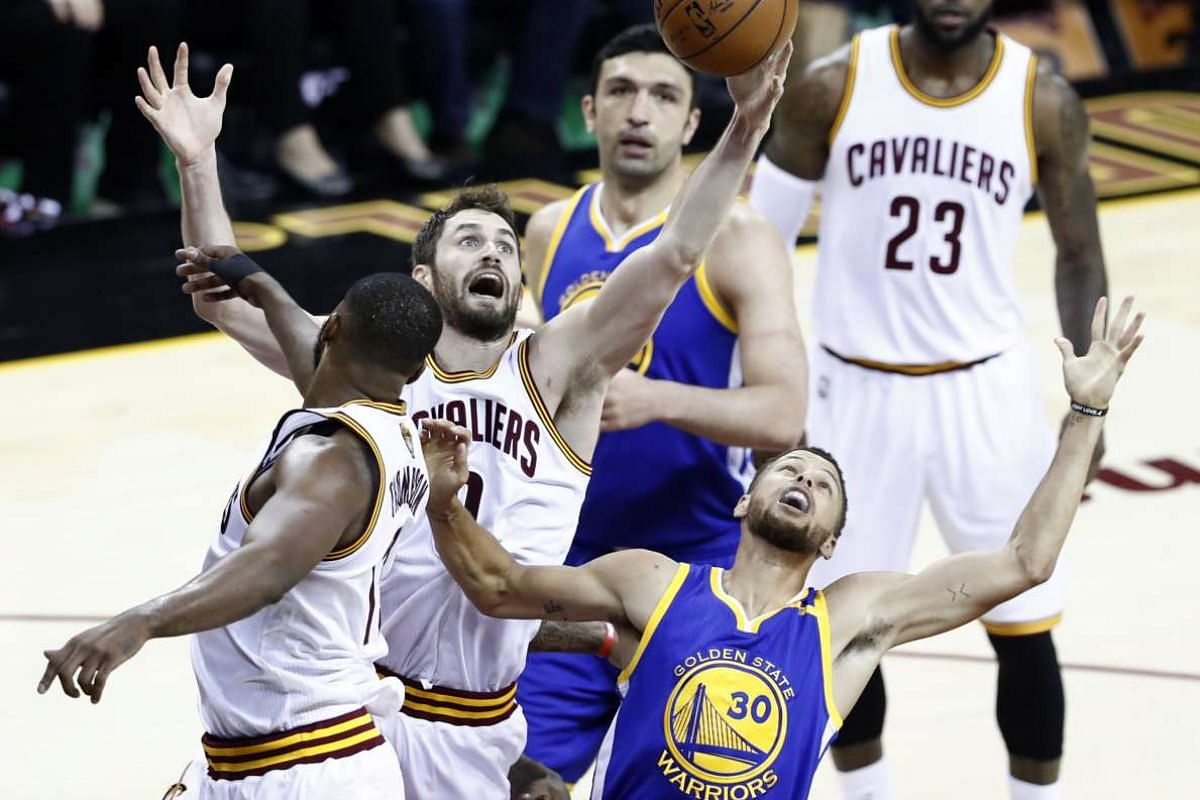 Cleveland Cavaliers forward Kevin Love (L-Center) and Golden State Warriors guard Stephen Curry (R) reach up for a rebound in the first half of game.